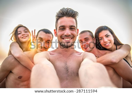 Multiethnic group of friends enjoying vacation  and taking a picture with camera - Mixed group of several people having fun on the beach at sunset - stock photo