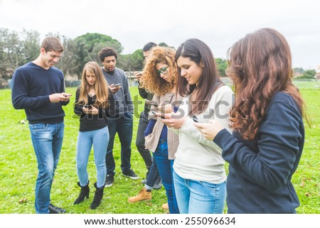 Multiethnic group of friends looking at their own smart phone. Technology, internet and social network addicion concepts, modern social issues. - stock photo