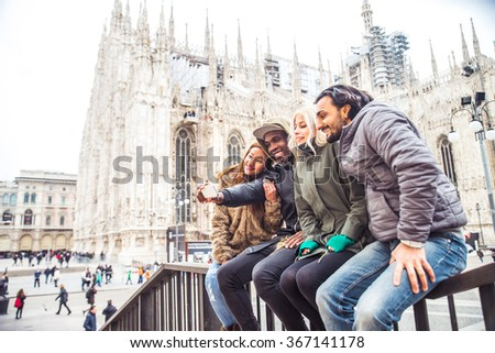 Multiethnic group of friends taking a selfie with smart phone to share on a social network - people of diverse ethnic having fun outdoors, Milan's Duomo cathedral in the background - stock photo
