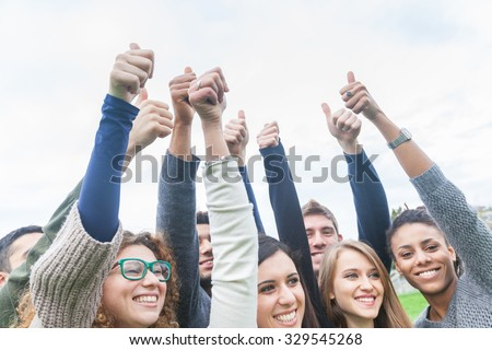 Multiethnic group of friends with thumbs up. They are at park, standing side by side, with smiling and happy faces. Success and teamwork concepts. - stock photo