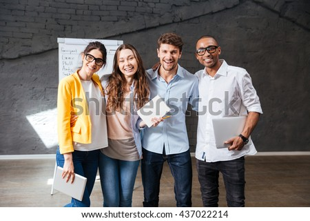 Multiethnic group of happy young business people holding tablet and laptop standing in office - stock photo