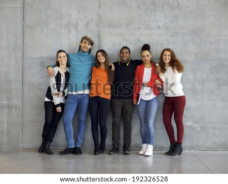 Multiethnic group of happy young university students on campus. Mixed race young people standing together against wall in college. - stock photo