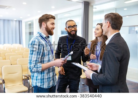 Multiethnic group of inspired young people standing and discussing new project in conference room  - stock photo