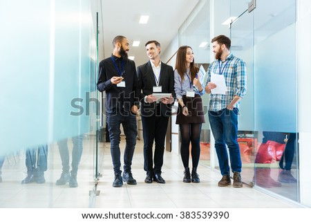 Multiethnic group of smiling business people standing in the office - stock photo