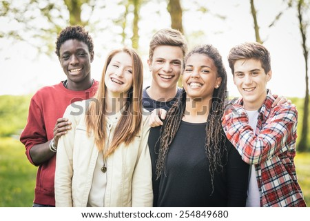 Multiethnic group of teenagers outdoor. They are embraced at park, two boys and one girl are caucasian, one boy and one girl are black. Friendship, immigration, integration and multicultural concepts.