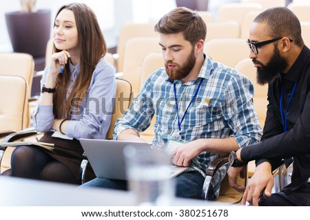Multiethnic group of young business people using laptop sitting on meeting in conference hall - stock photo