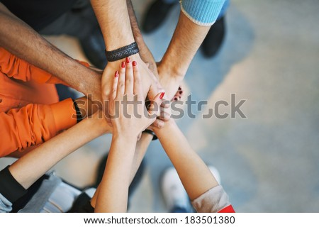 Multiethnic group of young people putting their hands on top of each other. Close up image of young students making a stack of hands. - stock photo