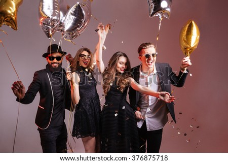 Multiethnic group of young smiling people dancing and having  party over colorful background - stock photo