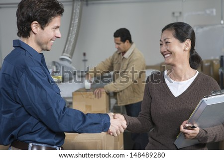 Multiethnic man and woman shaking hands in distribution warehouse - stock photo