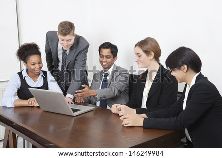 Multiethnic professionals using laptop at conference room - stock photo