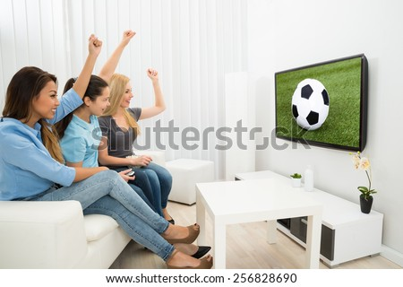 Multiethnic Women Sitting On Couch Cheering Watching Football Match - stock photo