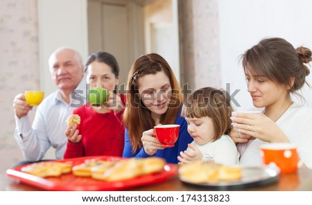 multigeneration family drinks tea at home