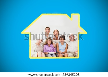 Multigeneration family on couch watching tv against blue background with vignette - stock photo