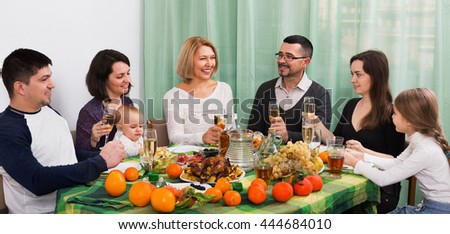 Multigenerational big family sitting at holiday table, toasting and smiling