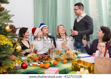 Multigenerational cheerful family sitting at festive table near Christmas tree - stock photo