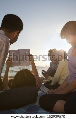 Multigenerational family relaxing and reading on the beach - stock photo