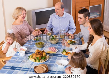 Multigenerational family sitting and talking at the table set for dinner