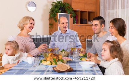 Multigenerational family sitting at the table set for dinner together