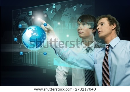 Multimedia. Happy young couple touching high-tech 3d earth panel - stock photo