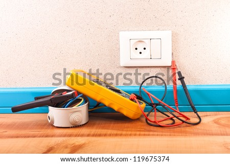 Multimeter, electrical box, wire stripper in the room - stock photo