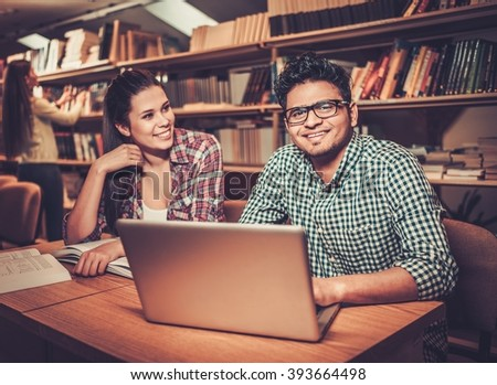 Multinational group of cheerful students studying in the university library. - stock photo