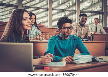 Multinational group of cheerful students taking an active part in a lesson while sitting in a lecture hall. - stock photo