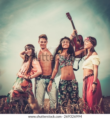 Multinational hippie friends with guitar in a wheat field  - stock photo