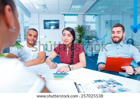 Multinational team. Group of international young people in smart casual discussing analytical data while working in creative space  - stock photo