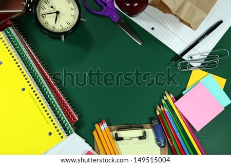 Multiple Back to School Items Arranged on a Green Blackboard - stock photo