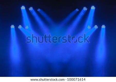 Multiple blue LED spotlights with criss-crossing beams lighting an empty stage. - stock photo