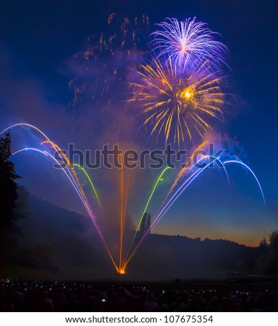 Multiple burst colorful fireworks explosion display against dark blue sky - stock photo