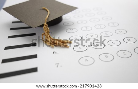 Multiple choice exam with mini graduation cap                                - stock photo