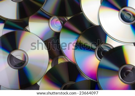 Multiple compact disks overlapping each other, creating a colourful display