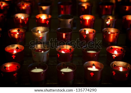 Multiple devotional candles lighting a darkened Roman Catholic Basilica. Image shows candle holders most all with lit candles. The lit candles provided the only light for this shot. - stock photo