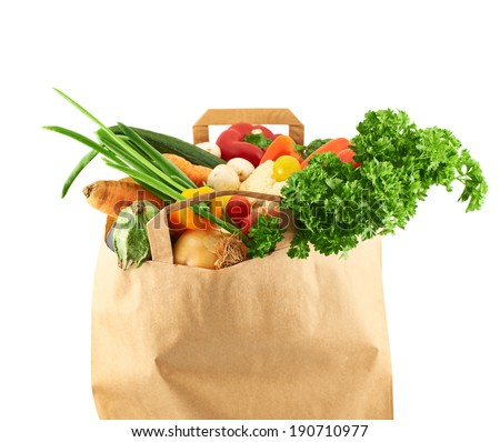 Multiple different vegetables in the paper bag isolated over the white background