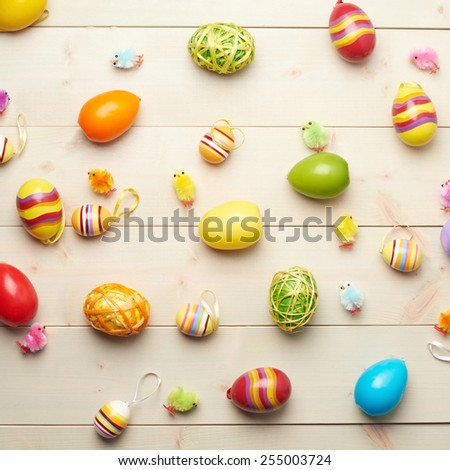 Multiple Easter egg decorations scattered over the wooden surface as a festive background composition - stock photo