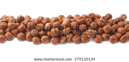 Multiple hazelnuts aligned in a line as copyspace background composition isolated over the white background - stock photo