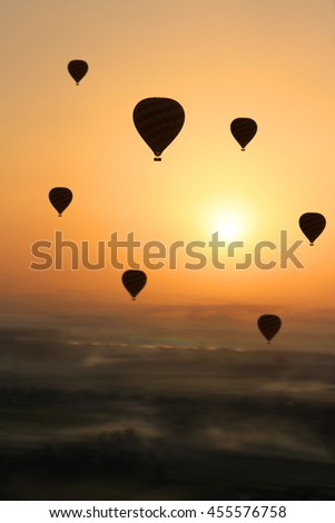 Multiple Hot air balloons silhouetted in the  early morning sun during  flight, with foggy patches in the Valley of the Kings, Egypt, Africa - stock photo