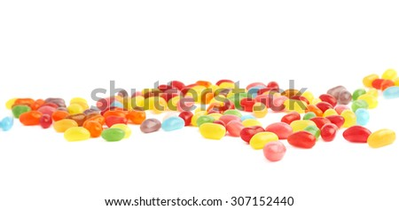 Multiple jelly bean candy sweets spilled over the white surface as a background composition - stock photo