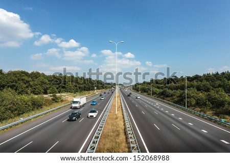 Multiple lane highway in The Netherlands against a blue sky with few clouds - stock photo