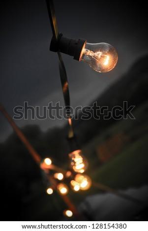 Multiple light bulbs on string bokeh - stock photo