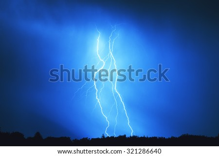 Multiple lightning bolt hits the ground at night - stock photo