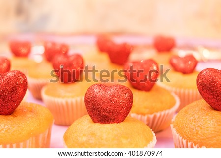 Multiple muffins decorated with multicolored frosting, cocoa powder and beans, candies and whipped cream side view toned selective focus - stock photo