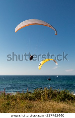 Multiple paragliders with their parachutes on a sunny day.