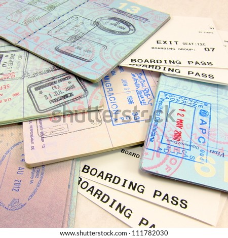 Multiple passports, multiple passport stamps, and airline boarding passes - stock photo