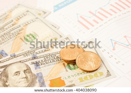 Multiple scattered American 100 dollar banknotes and graph in full frame coverage with corner vignetting viewed from above in a conceptual financial background