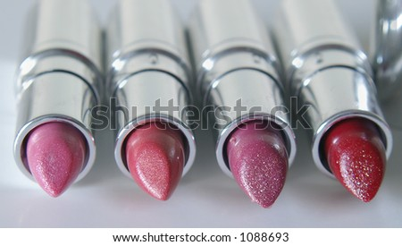 Multiple shades of lipstick in shiny silver tubes. - stock photo