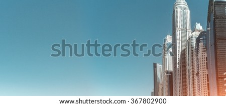Multiple skyscrapers in sunny day, view from the bottom, blue sky background - stock photo