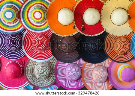 multiple summer beach hats displayed on a colorful wall - stock photo