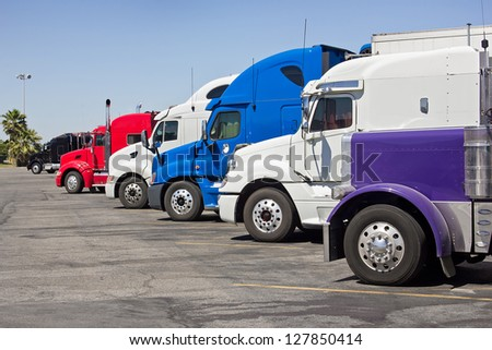 Multiple trucks park in a large parking lot.